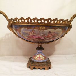 Rare Sevres centerpiece with bronze mounts artist signed V. Benis, Chateau de Tuileries, hand painted with cherub and lady on the front,. ca-1846, 19 inches by 11 1/2 inches with bronze mounts and masked women face handles. Price on Request.
