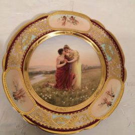 Royal Vienna plate painted with lovers and a border of three medallions of cherubs and raised gilding. artist signed Fritsch, under glaze blue beehive mark: 9 1/2 inches.  Sold.