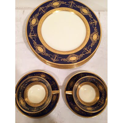Five cobalt Minton dinner plates and two cream soups and saucers, all with profuse raised gilding.