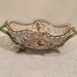 Pair of KPM reticulated baskets with raised flowers and flowers and birds, each painted differently on raised feet, having bird medallions on each side, 12 1/2 inches long by 8 inches deep. Price on Request