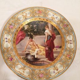 Royal Vienna plate with painting of two ladies and a bird on a veranda, with raised gilding and flower borders, under glaze blue beehive mark, late 19th century, Price on Request, 9 1/2 inches