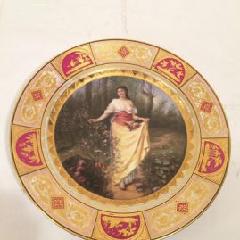 Royal Vienna plate of lady with long dress in the woodlands, with raised gilding in the border decoration.Has under glaze blue beehive mark; artist signed P. Schumacher.  Late 19th century, Price on Request