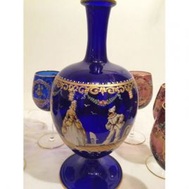 Lobmeyr decanter and six wine goblets of which 3 goblets are cobalt blue and three goblets are amethyst colored. The decanter is decorated with ladies and harlequins. Goblets are painted each differently with different ladies and gentlemen. Sold.