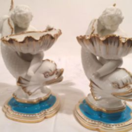 Two Minton master salts with figures of cherubs and dolphins.. 7 inches tall by 4 inches wide. Late 19th century. Price on Request