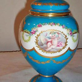 Other side of Minton cherub vase in the style of Sevres with rose finial