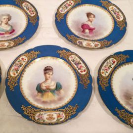 Set of 12 rare Sevres celeste blue portrait plates, each painted with a different portraits of famous French women many of the French court with three flower bouquet cartouches and raised gilding. diameter 9 1/8 inches. Price on Request.