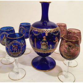 Another view of the set of the Lobmeyr decanter and six wine goblets of which 3 goblets are cobalt blue and three goblets are amethyst colored. The decanter is decorated with ladies and harlequins. Goblets are painted each differently with different ladies and gentlemen. Sold.