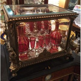 Rare bronze and beveled glass tantalus flanked with a figural putti on each corner. Inside the tantalus is cranberry Saint Louis crystal including four decanters and eleven cordial glasses. Must be seen to be appreciated. Sold.