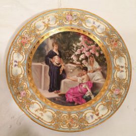 Royal Vienna plate of three ladies in a garden with one lady playing the harp, with raised gold and flowered border, under glaze blue beehive mark,  9 1/2 inches, Price on Request