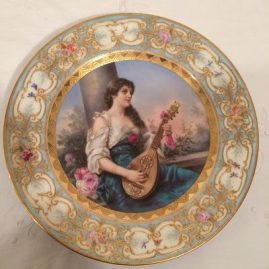 Royal Vienna plate of beautiful lady playing the mandolin with raised gilding and flowers around the border, artist signed Wagner, under glaze blue beehive mark, 9 1/2 inches; Price on Request