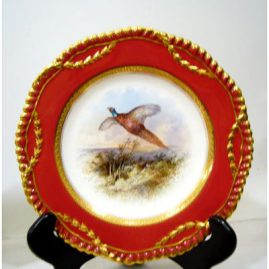 Close up of Wedgwood bird plate from the plates in the top row. Each is artist signed J. H Plumber