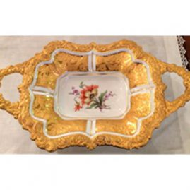 Two handled Meissen gilded charger with orange flower painting, and raised gold flower and leaf decoration. 13 3/4 inches wide by 8 1/4 inches tall. Circa-1923-1933. Sold.