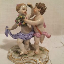 Meissen figurine of boy and girl putti dancing with flowers. Circa 1880s, Height-5 inches tall by 4 1/4 inches wide. Price on Request