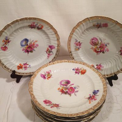 Set of nine KPM dinner plates, each painted with different bouquets of flowers