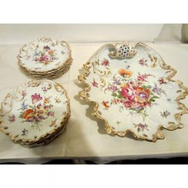 Beautiful Dresden set with twelve dessert plates and rare platter. Each plate is painted differently with different bouquets of flowers. All plates and platter have 9 holes or reticulations around the edges. Plattter is 14 1/2 inches long and 12 3/4 inches wide. Plates are 7 1/8 inches. Late 19th century. Sold