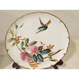 Close up of one of the set of eight George Jones rose and hummingbird plates. Late 19th century. 9 inches. Each are painted differently with different roses and hummingbirds. The paint and design is raised. Roses painted in pink, red, yellow and white. Sold