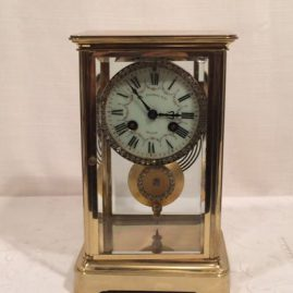 French late nineteenth century brass and glass clock with beveled glass on front and sides