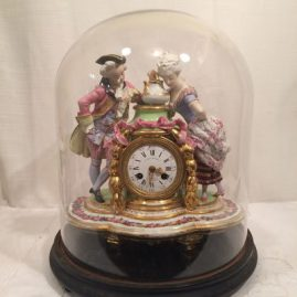 French figural clock with glass dome and wooden base. Late 19th century