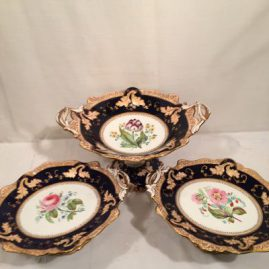 Set of three cobalt with flower bouquets Copeland and Garrett compotes, Circa-before 1850s, Large compote with tulip is 14 1/4 inches wide by 11 3/4 inches deep and 4 5/8 inches tall, pair of compotes are 12 inches wide by 9 1/2 inches deep by 4 5/8 inches tall. Each are painted with different flowers. Sold