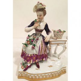 Meissen figurine of lady smelling flowers representing the sense of smell.