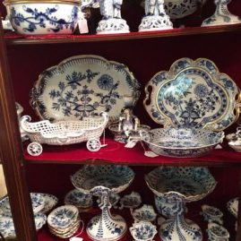 Showcase showing a selection of antique Meissen blue onion china like Meissen trays, reticulated bowls, reticulated compotes and selection of salt cellars. Please look at the gallery to see the items in detail.