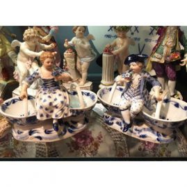 Pair of Meissen blue onion double salt cellars with figures of a boy and girl.
