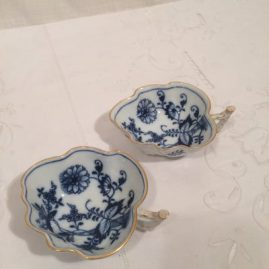 Eleven Meissen blue onion leaf bowls with gilded rim. Length-4 3/4 inches by 1 1/2 inches tall. Price on Request.