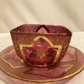 Set of six cranberry Moser bowls and under plates with heavy gilding. Bowls are 3 7/8 inches wide and under plates are 6 5/8 inches in diameter. Price on Request.