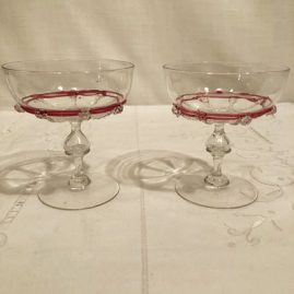 Set of five Salviati Venetian champagnes or coupes with raised pink ribbon glass decoration and applied crystal balls. Each is 4 1/4 inches tall. Price on Request.