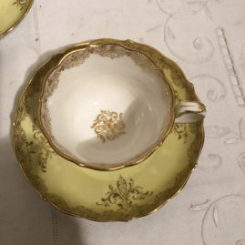 Inside of yellow Meissen cup and saucer with paintings of lovers