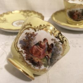One of ten Meissen yellow cup and saucers with lovers